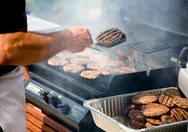 Person Flipping Burgers During BBQ