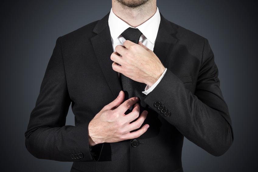 businessman correcting tie